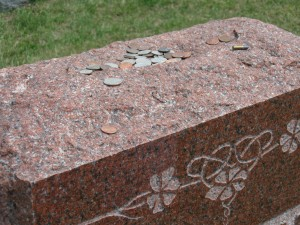 Coins and a bullet left on the top of the stone.